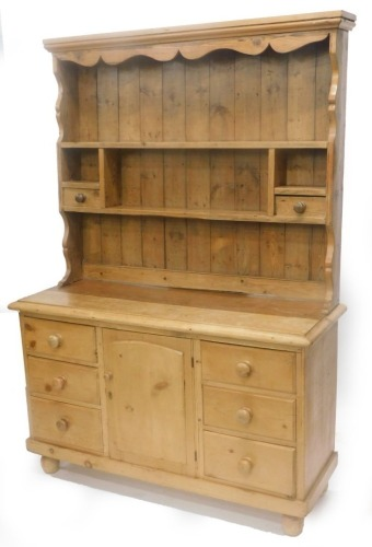 A pine dresser, the associated raised back with various shelves and two drawers, the base with a moulded edge above six drawers and an arched door, on turned feet, 196cm high, 137cm wide.