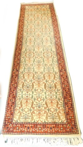 A Persian type runner, with a design of scrolls, flowers, etc., on a cream ground with one wide and two narrow borders, 301cm x 87cm.