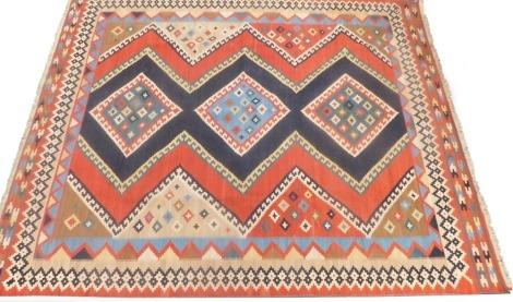 A Kilim rug, with a geometric design in cream, blue, navy, etc., 182cm x 229cm.