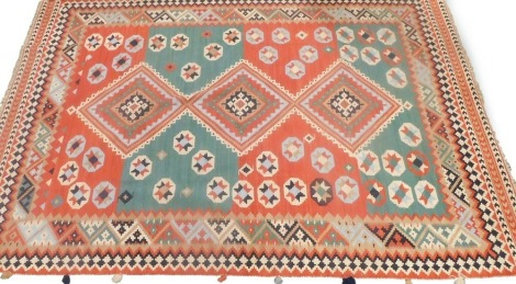 A Kilim rug, with a geometric design in green, blue, navy cream, etc., 199cm x 294cm.