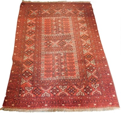 A Balouch type rug, with a design of medallions, on a red ground with multiple borders, 243cm x 171cm.