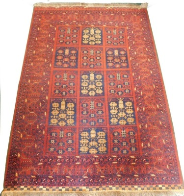 A Balouch type rug, with a design of medallions, in navy and cream on a red ground with multiple borders, 207cm x 143cm.