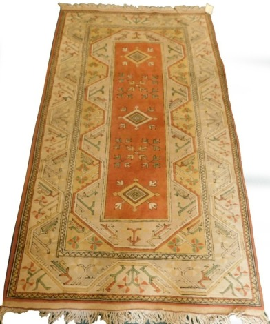 A Turkish rug, with a multi coloured geometric design, on a cream ground with multiple borders, 216cm x 123cm.