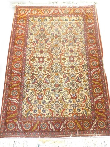 A Persian rug, with an all over design on a cream ground with one wide, two narrow borders, 143cm x 98cm.