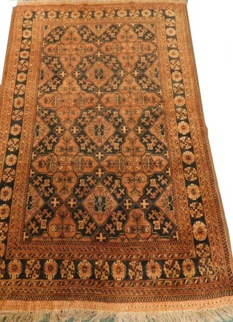 A Balouch type rug, with a design of medallions, in rust coloured medallions on a navy ground with multiple borders, 195cm x 125cm.