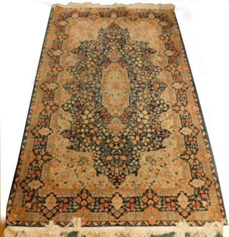 A Persian rug, with a design, decorated with flowers in navy, surrounded by cream and pale blue spandrels, and with multiple borders, 240cm x 152cm.