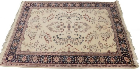 A Persian style rug, with a design of flowers on a cream ground with one wide and multiple borders, 188cm x 227cm.