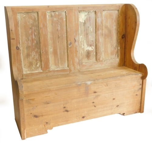A pine settle, with a panel back, shaped sides, 138cm wide.