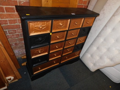 A black and gold painted bank of drawers, with Egyptian style carving.