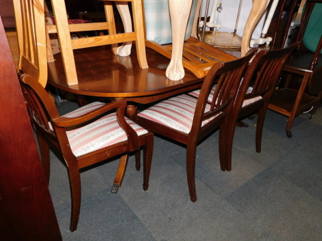 A reproduction mahogany dining table, together with five chairs. (6) The upholstery in this lot does not comply with the 1988 (Fire & Fire Furnishing) Regulations, unless sold to a known exporter or upholsterer it will be cut from the frame before leaving
