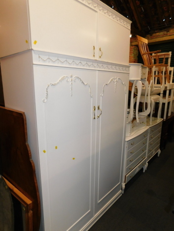 A French style cream painted bedroom suite, comprising two dressing tables and stools, two chests, wardrobe and two bedside cabinets. (9)