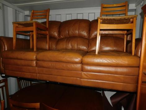 A tan leather three seater sofa.