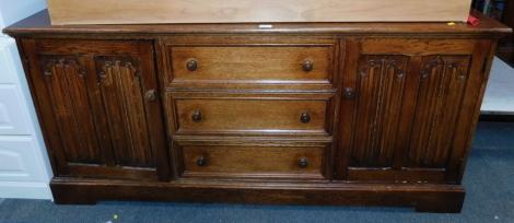 An oak veneered sideboard, of three drawers flanked by linenfold cupboard doors.