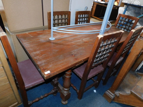A Spanish pine dining table, with turned and splayed legs, with central iron stretcher, together with six chairs with bobbin turned back rests. (7)
