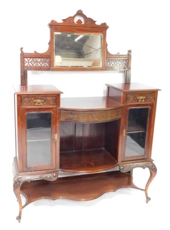 A Victorian mahogany mirror back display cabinet, the raised back with a rectangular mirrored plate, flanked by blind fret panels, the stepped base with a bow fronted centre section, flanked by an arrangement of two drawers and two glazed doors, above a r