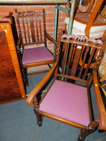 A pair of early 20thC oak carver dining chairs, with crown carved back rails, raised on barley twist legs.