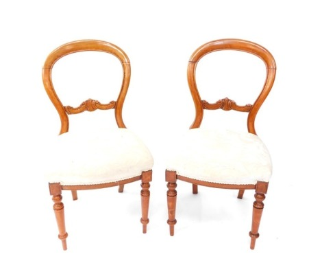 A pair of Victorian balloon back chairs, each with heavily carved horizontal scroll splats, and overstuffed seats in cream material, on turned front legs, 86cm high. (2)