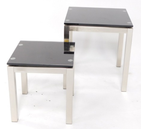 A pair of graduated brushed metal and smoked glass occasional tables, each of plain form, 56cm high, 50cm wide, and 43cm high, 40cm wide respectively.