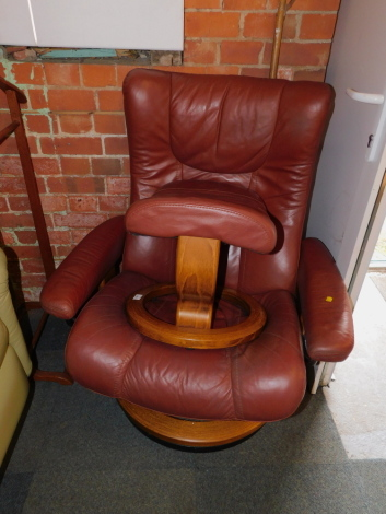 An Ekornes Stressless reclining armchair, in maroon leatherette, together with a matching footstool. (2)