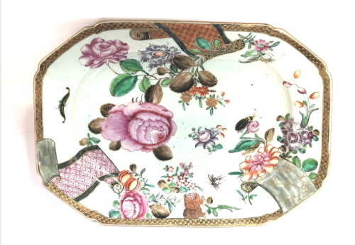 An 18thC Chinese porcelain rectangular serving plate, with diaper work border having three scroll lappets, enamelled with peonies and insects, enriched in gilt, 29cm wide.