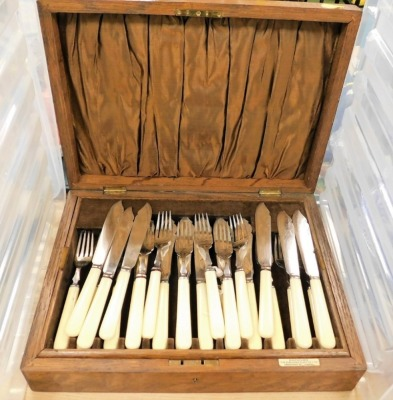 A bone handled cased set of twelve fish knives and forks, each by Alan Clarke and Co, over two tiers, together with an additional part set of six, in a Alexander Clarke Company of London oak box, 8cm high, 36cm wide, 26cm deep.