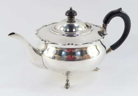 A George V silver teapot, with fluted top and ebonised knop and handle, on tripod base, makers stamp Sheffield 1923, 20oz gross.