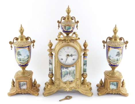 A Imperial gilt metal garniture suite, comprising mantel clock stamped Imperial Italy, with printed panels of buildings and figures, in blue and gilt, with two matching urns, the clock 41cm high, the urns 32cm high.