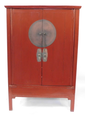 A Chinese 19thC red lacquer marriage cupboard, the outswept pediment over a pair of doors opening to reveal a shelf, above two frieze drawers, with recess below, raised on stile feet, 172cm high, 111cm wide, 61cm deep.