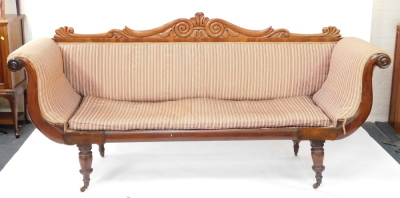 A Regency flame mahogany scrolling sofa, with a foliate carved back, blue and white patterned fabric, raised on turned legs, brass capped on castors, 225cm wide. - 2