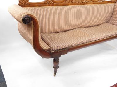 A Regency flame mahogany scrolling sofa, with a foliate carved back, blue and white patterned fabric, raised on turned legs, brass capped on castors, 225cm wide. - 4