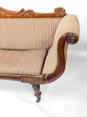 A Regency flame mahogany scrolling sofa, with a foliate carved back, blue and white patterned fabric, raised on turned legs, brass capped on castors, 225cm wide. - 5