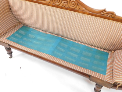 A Regency flame mahogany scrolling sofa, with a foliate carved back, blue and white patterned fabric, raised on turned legs, brass capped on castors, 225cm wide. - 6