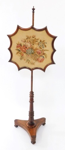 An early Victorian rosewood firescreen, the shaped screen with wool work floral tapestry, raised on a turned column, over a trefoil base, on three turned feet, 149cm high.