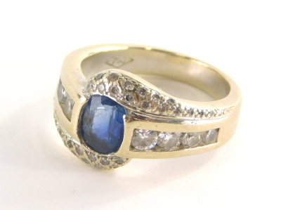 A sapphire and diamond dress ring, with oval sapphire in rub over setting, approx 1.43cts, white diamond set twist shoulders, with four round brilliant cut diamonds in tension setting, white metal, marked 750, ring size P½, 11.1g all in.