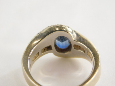 A sapphire and diamond dress ring, with oval sapphire in rub over setting, approx 1.43cts, white diamond set twist shoulders, with four round brilliant cut diamonds in tension setting, white metal, marked 750, ring size P½, 11.1g all in. - 2