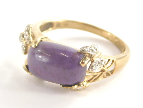 A 9ct gold dress ring, set with central purple rectangular cut stone, with butterfly details set with tiny diamonds, with pierced X frame shoulders, ring size U, 4.5g all in.