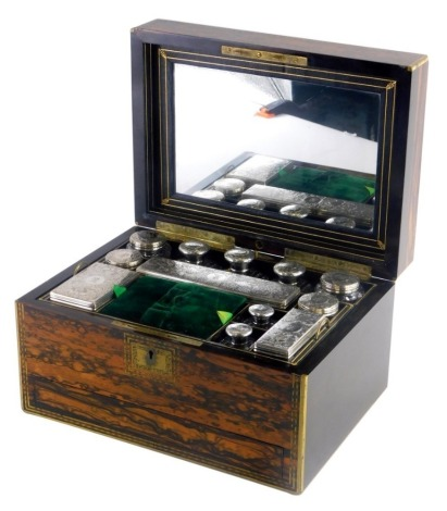 A 19thC coromandel and brass bound ladies dressing table box, the hinged lid revealing a fitted leather interior and a mirrored back, with an arrangement of silver topped cut glass bottles and boxes, each lid profusely decorated with a heraldic lion, scro