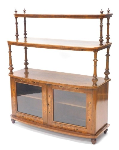 A Victorian figured walnut and marquetry whatnot cabinet, with two graduated bowfronted tiers, each on turned supports on finials, the base with two glazed doors, on bun feet, 125cm high, 106cm wide.