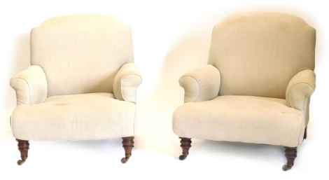 A pair of Victorian walnut Howard type armchairs, each upholstered in beige fabric and turned legs with ceramic castors, number stamped to rear legs.
