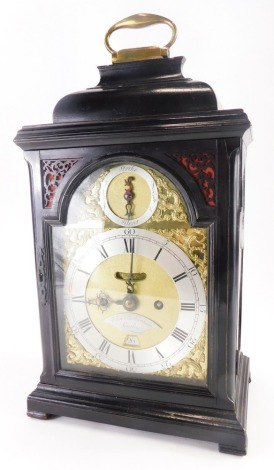 John Richardson, London. A George III ebonised bracket clock, the arched dial with silver chapter ring engraved with Roman numerals, gilt rococo scroll spandrels and strike silent subsidiary, the case with fret panels to the doors, canted corners on block