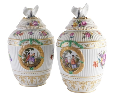 A pair of late 19th /early 20thC Berlin porcelain vases and covers, within laurel leaves, flower sprays, etc., with ribbed body, the cover with an eagle finial, marks in blue to underside, 38cm high.