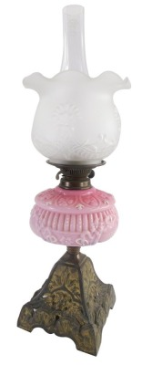 A Victorian cast iron oil lamp, with associated frosted shade, pink opaque moulded reservoir with white enamel decoration, the base decorated with masks, etc., 60cm high overall.