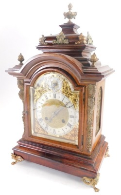 A late 19thC German rosewood mantel clock, with gilt metal mounts, the domed top embellished with flame finials, etc., above a arched brass dial with silvered chapter ring and pierced rococo cast spandrels flanked by caryatids, on paw feet, 48cm high.