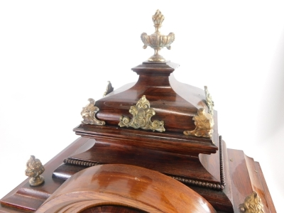A late 19thC German rosewood mantel clock, with gilt metal mounts, the domed top embellished with flame finials, etc., above a arched brass dial with silvered chapter ring and pierced rococo cast spandrels flanked by caryatids, on paw feet, 48cm high. - 2