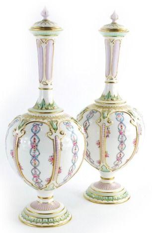 A pair of Royal Worcester porcelain bottle shaped vases and covers, each decorated with flowers, ribbons, etc., within compartments in Islamic style, on a domed foot, printed marks to underside, registration number 270100 numbered 1850, 33cm high.