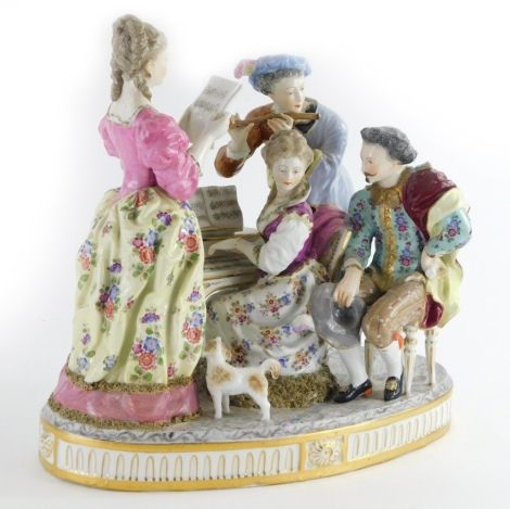 A late 19th/early 20thC continental porcelain figure group, modelled in the form of musicians around a piano with a small dog, picked out in coloured enamels, indistinctly cross swords type mark to underside, 33cm wide.