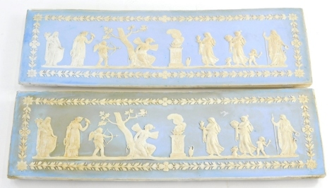 A pair of 19thC pale blue Jasperware plaques, each decorated with Neo Classical figures, trees, putti, etc. within oak leaf and acorn border, possibly Wedgwood, marks obscured, 46cm x 15cm.