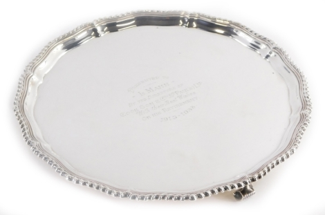 A George V silver salver, with a shaped and gadrooned border, the centre with the inscription 'Presented to L. Mann by the Directors of Cookson and Co. (St Pacil's) Ltd with Their Best Wishes on His Retirement 1913-1938', on three scroll feet, Birmingham