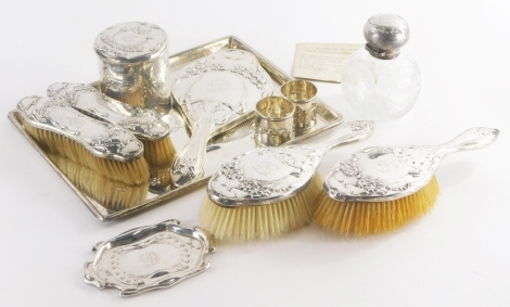 An Art Nouveau design silver dressing table set, comprising a large rectangular tray, decorated in typical Art Nouveau style with flowers, scrolls, etc., initialled D in the central cartouche, 31.5cm x 23cm, 18½oz, two silver backed hairbrushes and two cl