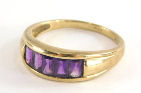 A 9ct gold half hoop dress ring, with five rectangular cut amethysts, in a tension setting on yellow metal band stamped 375, ring size U½, 4.3g all in.